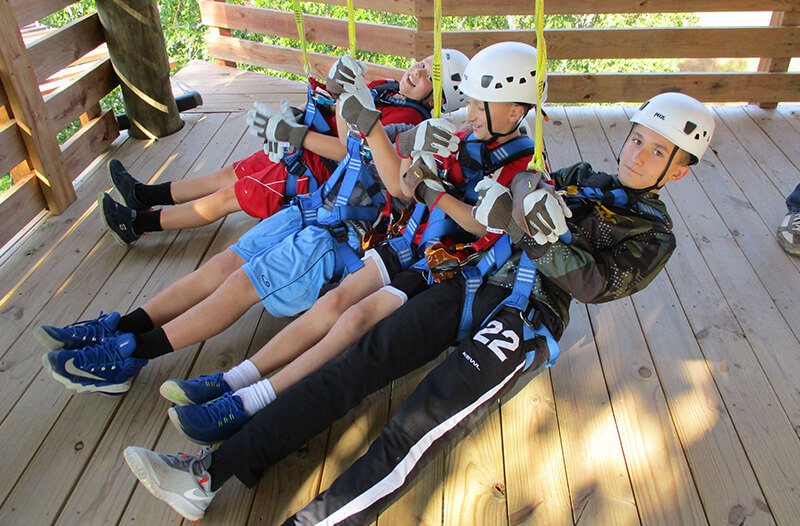 A young group of boys prepare to go on their zipline adventure
