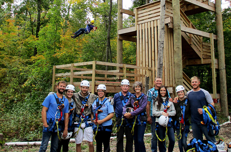 Group poses for picture while man zips above them