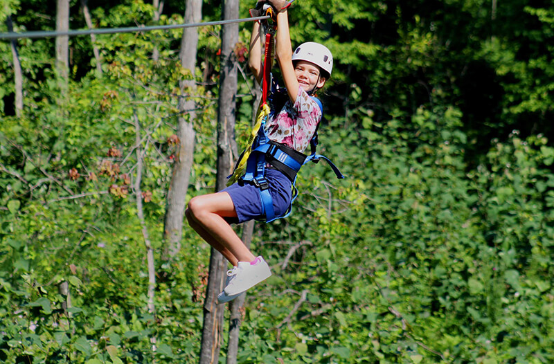 Young girl ziplines through the trees